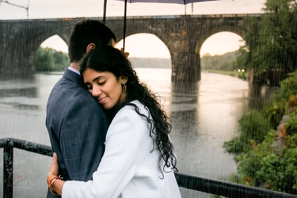 Girlfriend is hugging boyfriend under the umbrella during engagement session with South NJ Photographer Anett Mindermann Photography