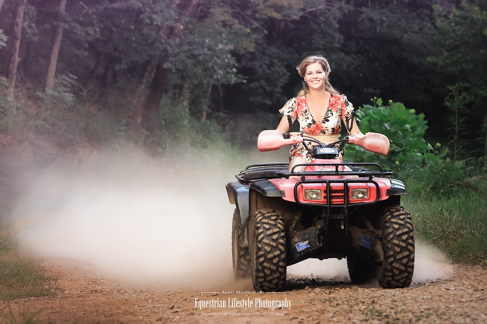 Girl is riding an ATV on a dusty off road
