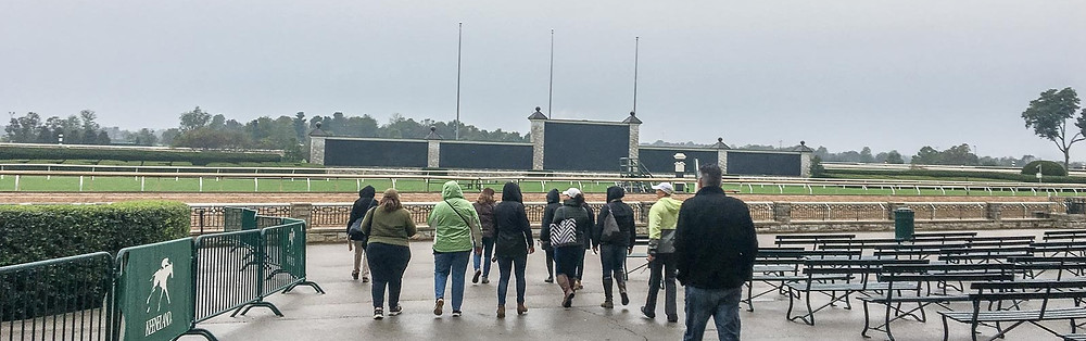 a group of people walking towards the racetrack in Keeneland