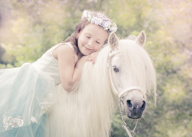 little girl in princess dress sitting on her pony snuggling up on him