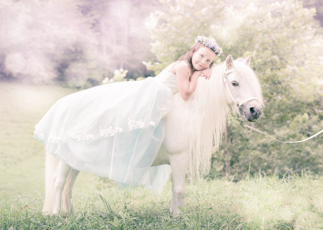 princess sitting on top of her white pony during photo shoot