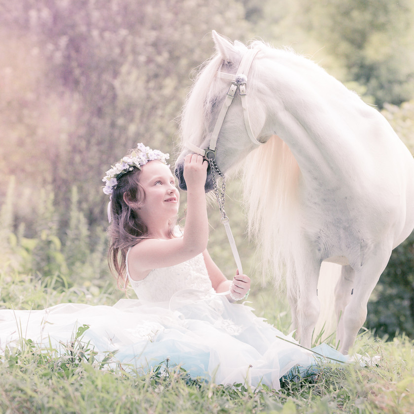 little princess sitting and looking at her white pony during photo session
