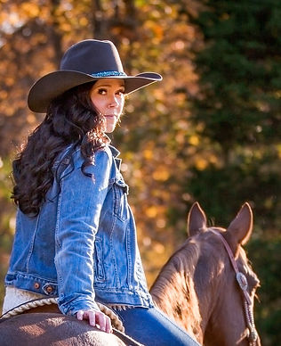 Cowgirl looking back over her shoulder on horse