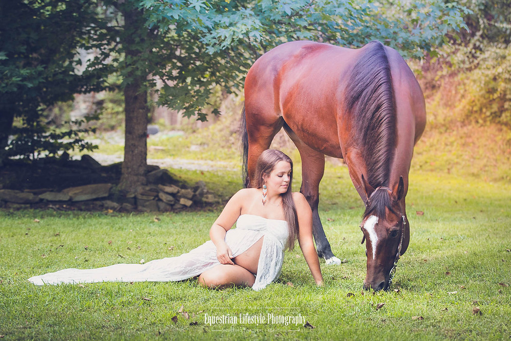 Young pregnant woman sitting on the grass next to her horse grazing