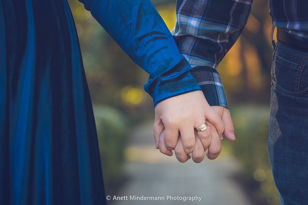 holding hands with Wedding ring in focus