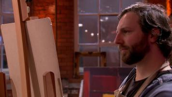 Close up of Chris looking at a canvas. The canvas is hidden from the viewers view.