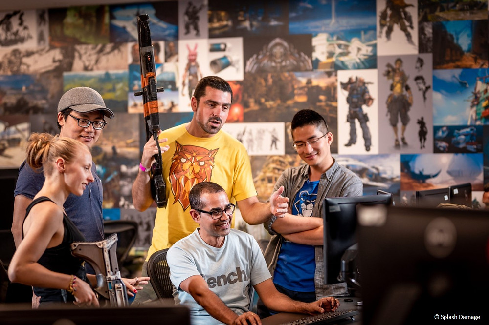 A group of 5 crowd around a computer. Two are holding model guns from their game.