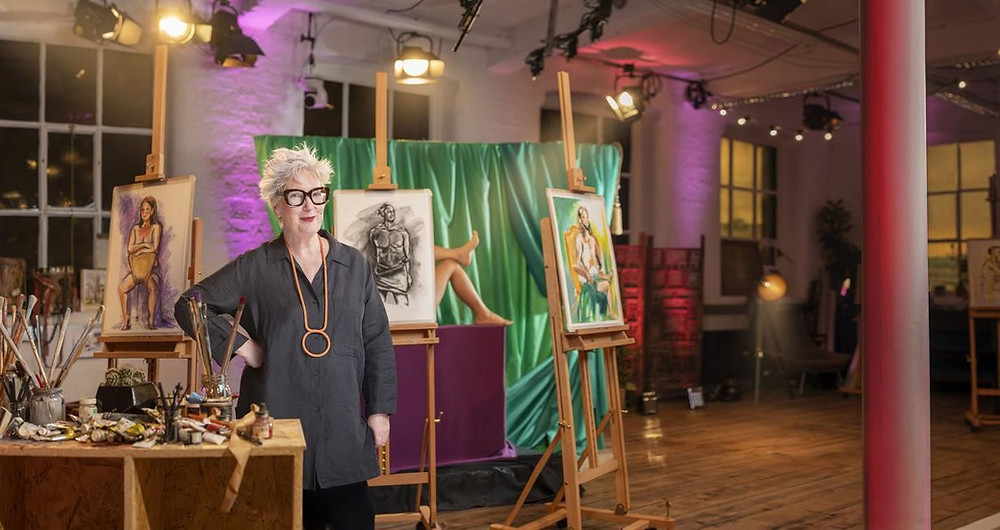 Jenny Eclair stands in front of several easels with life drawings on