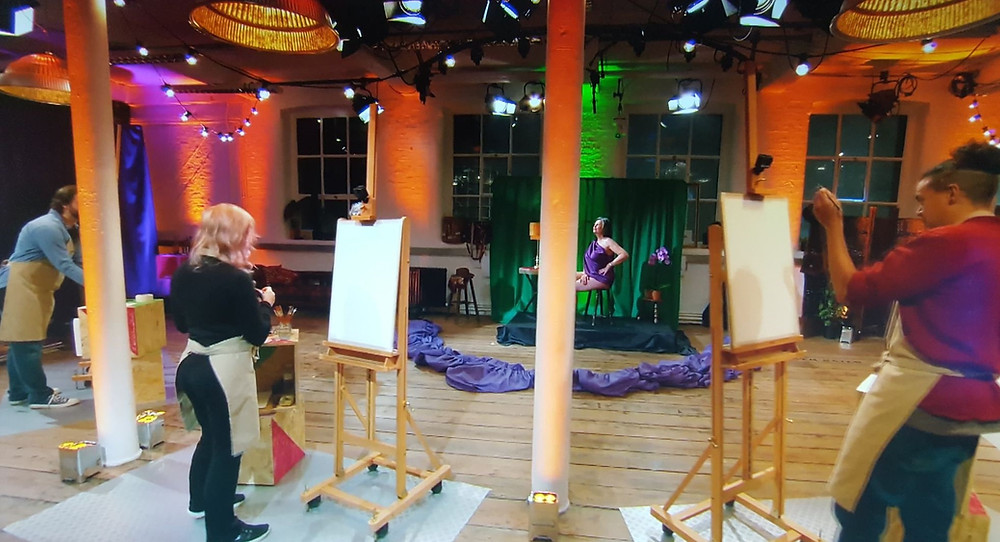 Four easels around a central model as artist start to draw on the canvases