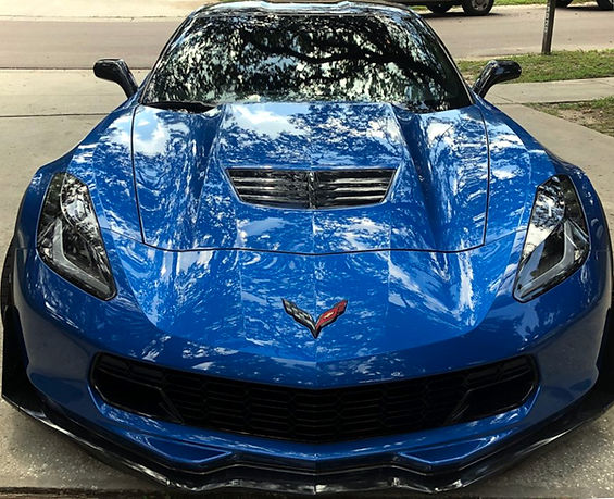 Ceramic coating of a blue sports car shining in the sun.