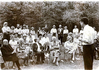 George Bates speaking in front of about 30 people, sitting in chairs or standing, on lawn with woods beyond