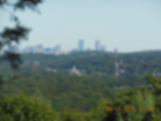 Distant view of Boston skyline from Doublet Hill, with rolling woods and a few buildings and towers in middleground