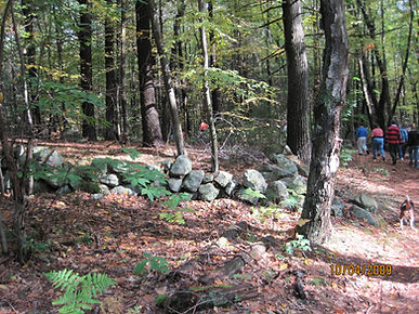 Stone wall in Highland Fores with people walking on trail at right
