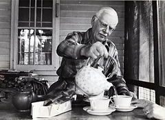 Dr. Elliston at a table on a porch, pouring tea into cups