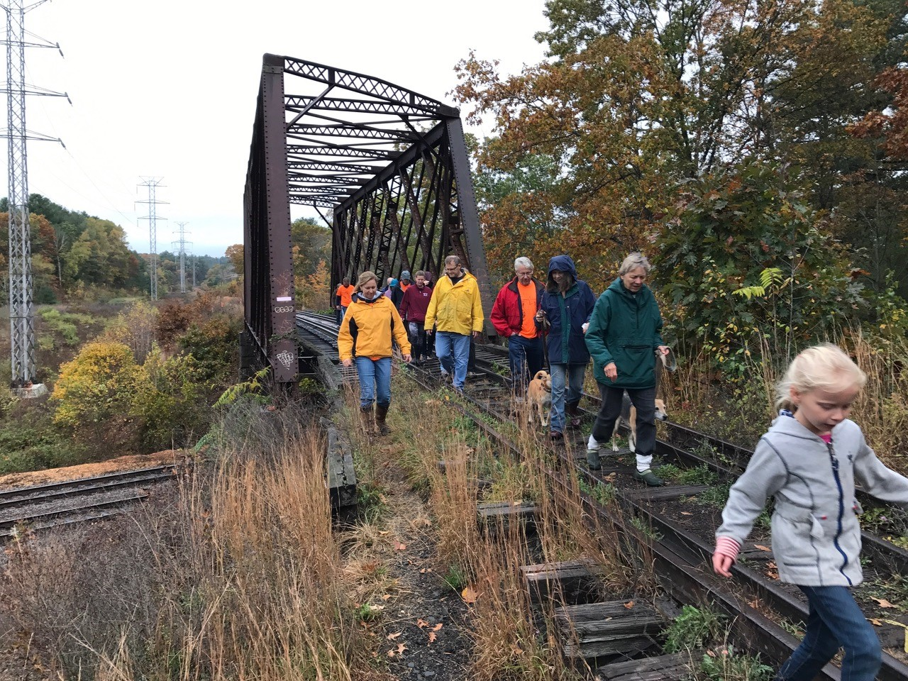 Walkers walking over the old trestle bridge over the Fitchburg Line