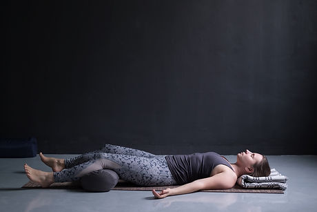 woman working out, doing yoga exercise on wooden floor, lying in Shavasana_edited.jpg