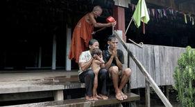 Monje purificando a una familia en su pagoda cerca de Stung Treng. Vuelta al mundo en bicicleta del fotógrafo humanitario Joseba Etxebarria.