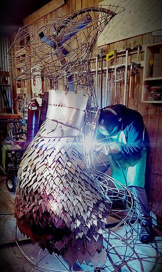 man sculpting large metal art