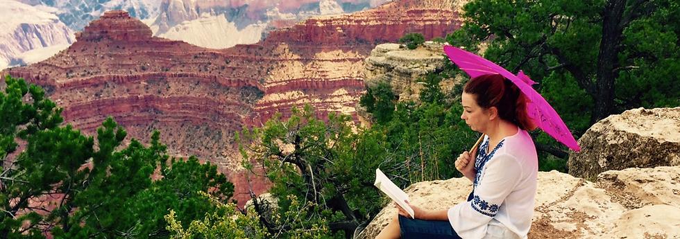 Christina Hoag reading at grand canyon cliff