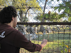 man looking on to a cemetery