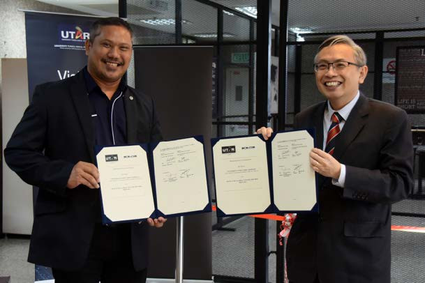 Prof Max Shangkar (left) and Prof Ewe with the signed documents.