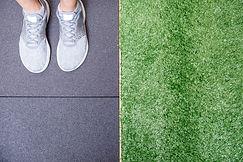Grey shoes standing on black stadium tra
