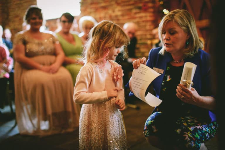 Lorraine Hull, Celebrant, handing wedding vows to the happy couple's daughter