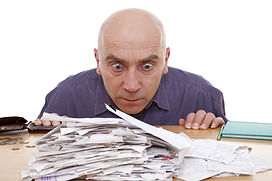 Man with distressed look on face as he is focused on a stack of unorganized paperwork.