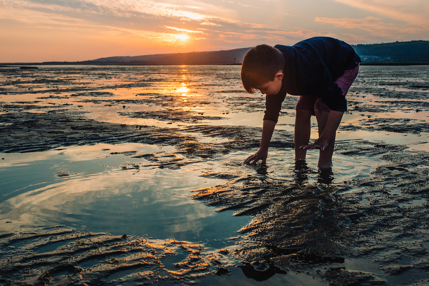 Outdoor picture of boy in the sunset, Llanelli beach