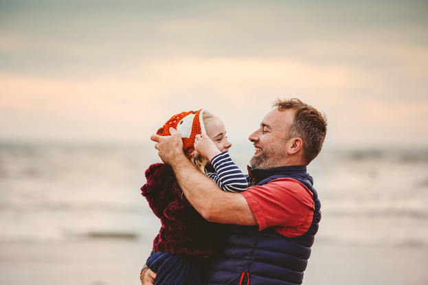 Natural outdoor family photograph of father and daughter in Pembrey beach