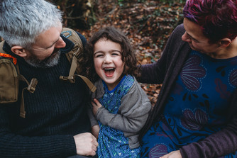 Family outdoor photograph ofparents with daughter, smiling, in Penllergaer Woods, Swansea