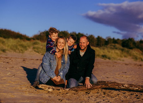 Outdoor family photograph of parents with two boys in Burry Port beach at sunset