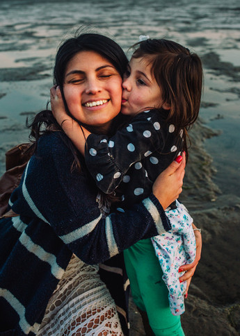 Natural outdoor photograph of mother and daugher hugging in Llanelli beach at sunset