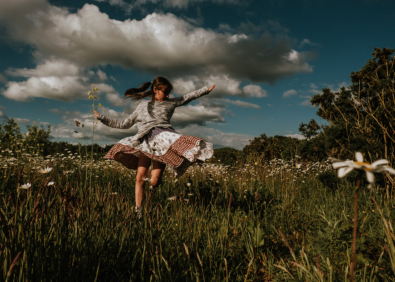 Outdoor photography of a girl dancing amongst daisies in Llanelli