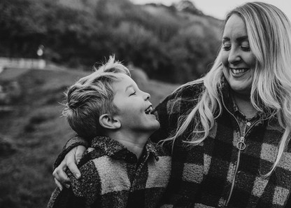 Natural outdoor photo of a mother and son smiling at each other, in Furnace Pond, Llanelli