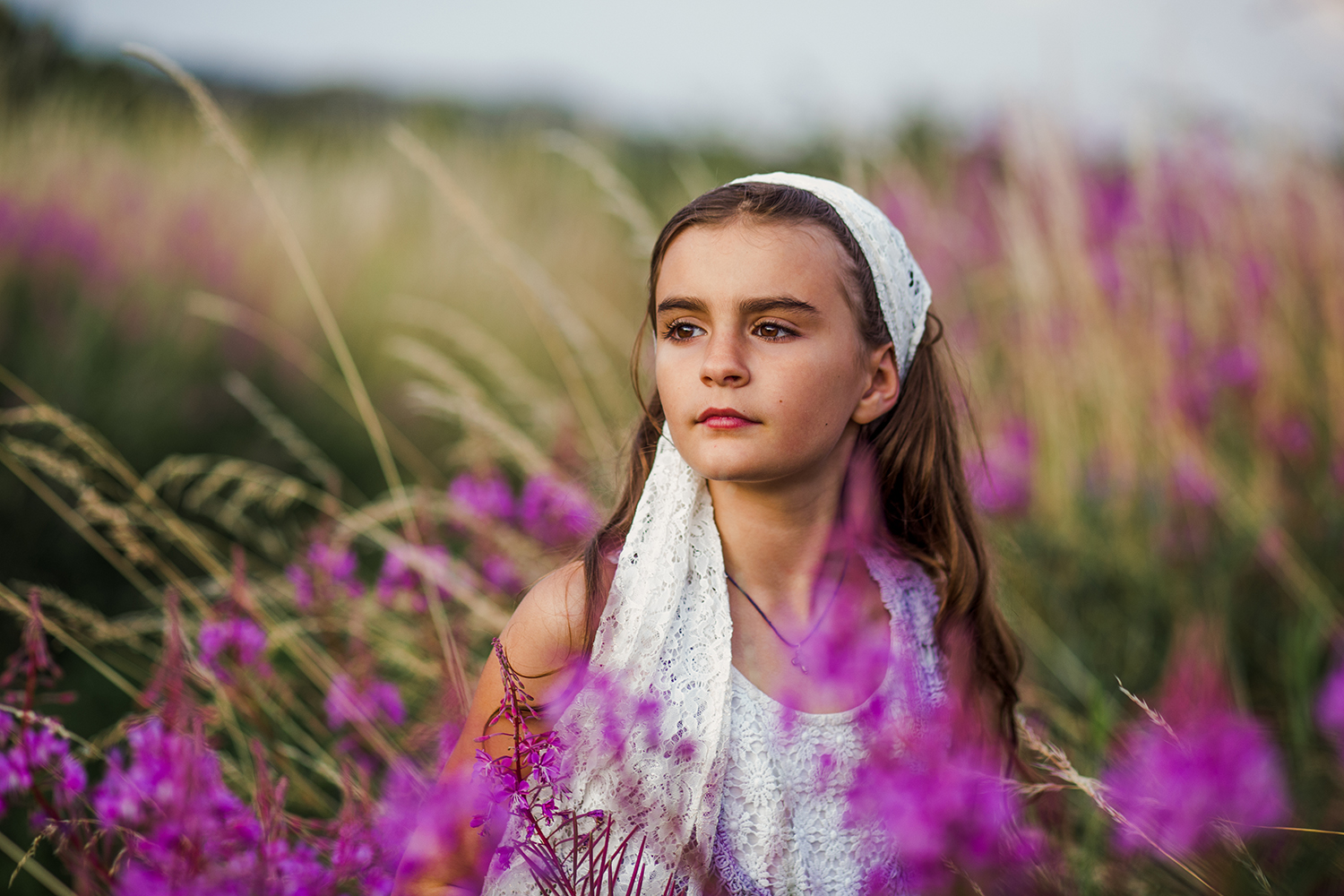 Outdoor portrait photography of a girl in Burry Port surrounded by pink summer flowers.
