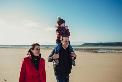 Family outdoor photograph of a couple with the dad carrying a boy on his shoulders, Three Cliffs, Swansea
