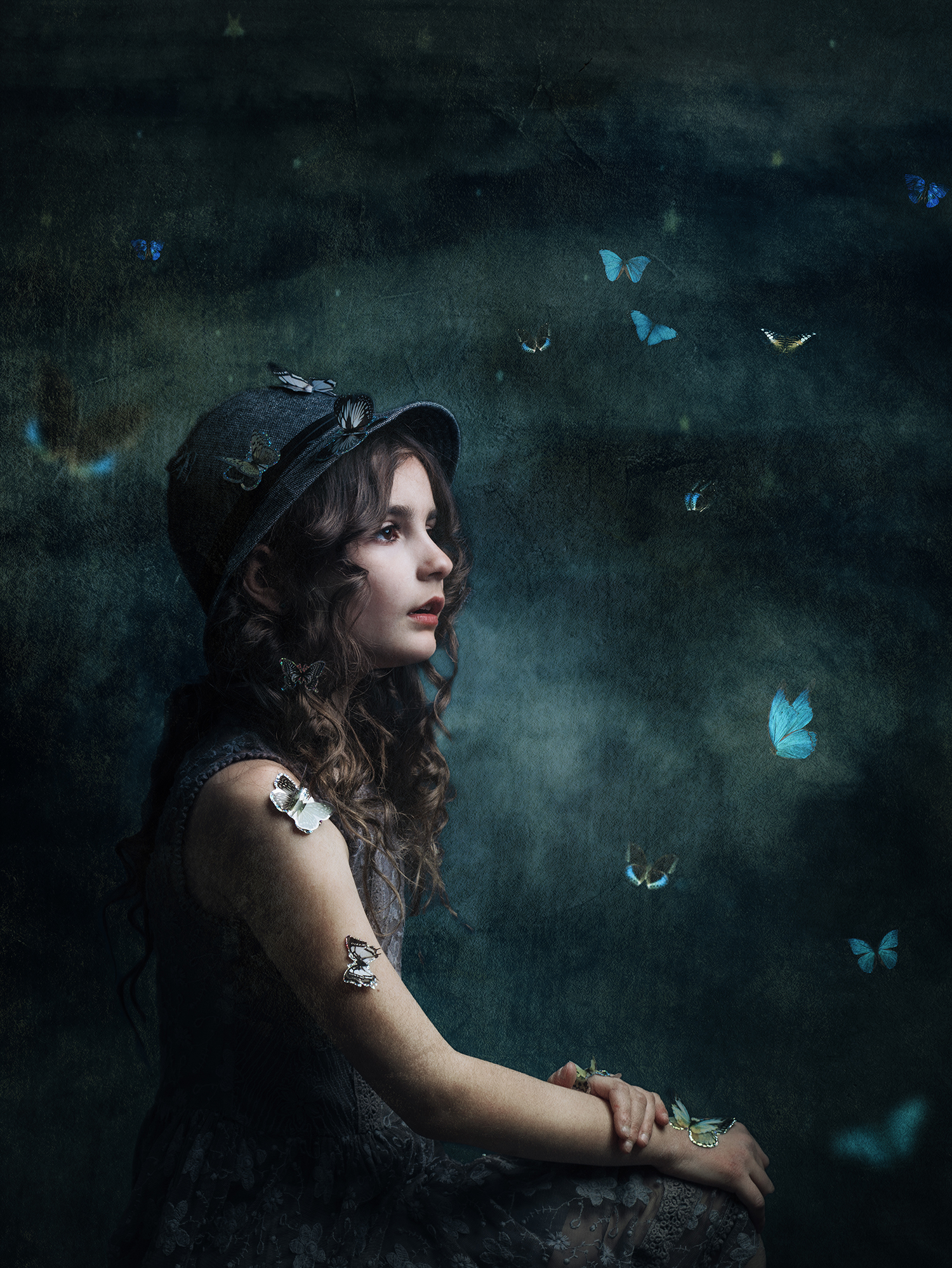 Dreamy fine art photograph of a girl surrounded by butterflies
