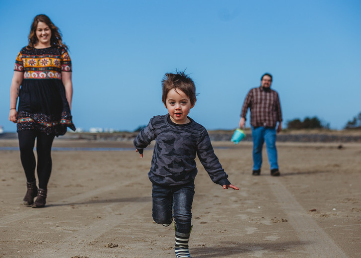 Family outdoor photography of a family with little boy running in Burry Port beach