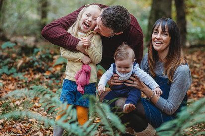 Outdoor relaxed family photograph of parents with two small children, laughing, Penllergaer Woods, Swansea