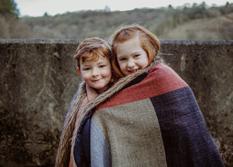 Family outdoor photograph of two siblings in a blaket in Swiss Valley Reservoir