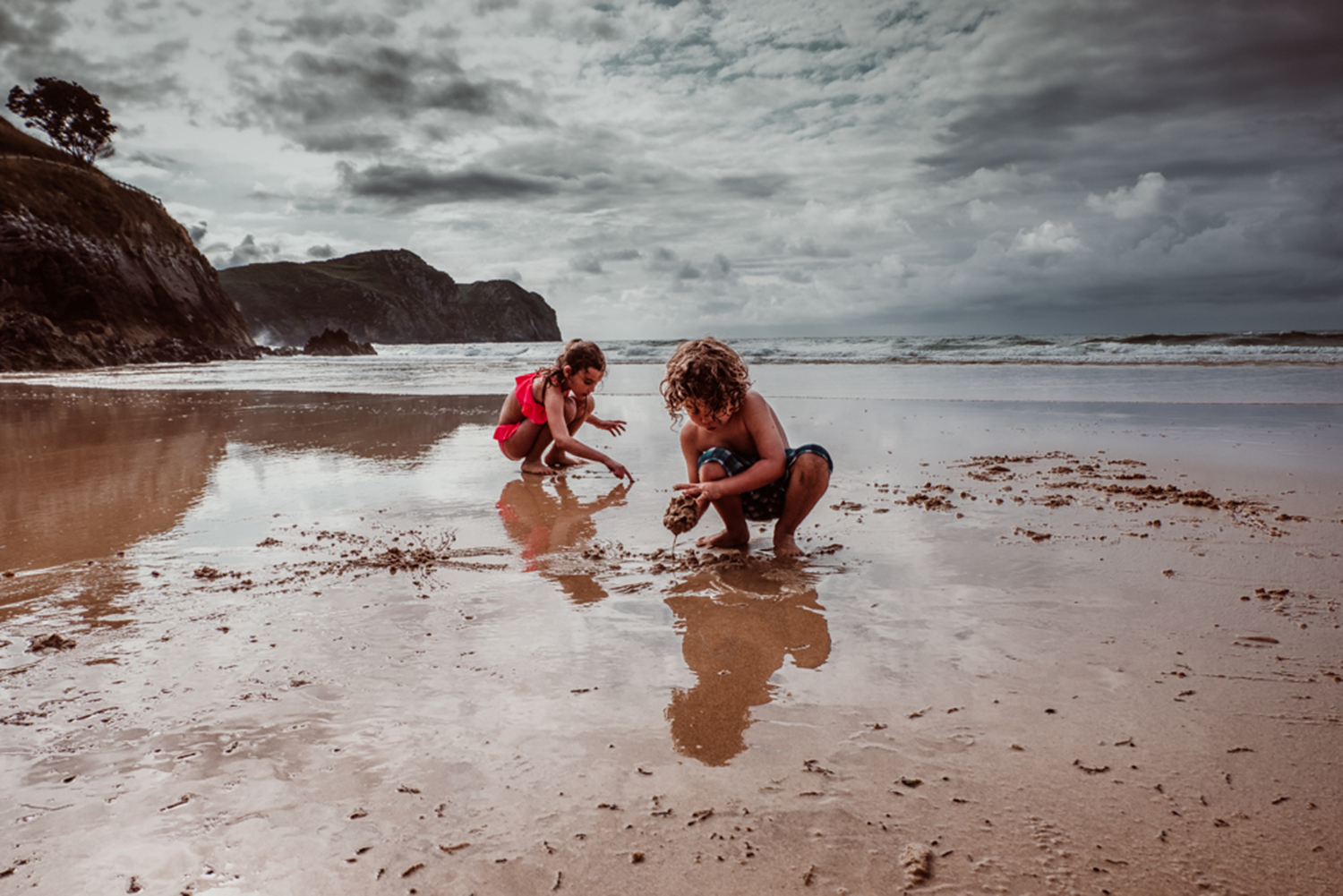 Outdoor photograph of two children playing at the beach.