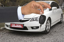 Male holding car keys with a rental car