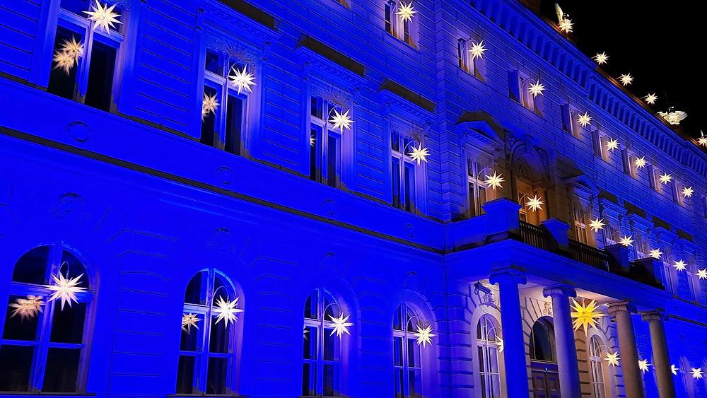 """Foto des Gebäudes """"Alte Kommandantur"""" in Berlin, Fassade in blau angestrahlt mit Sternen vor den Fenstern"""
