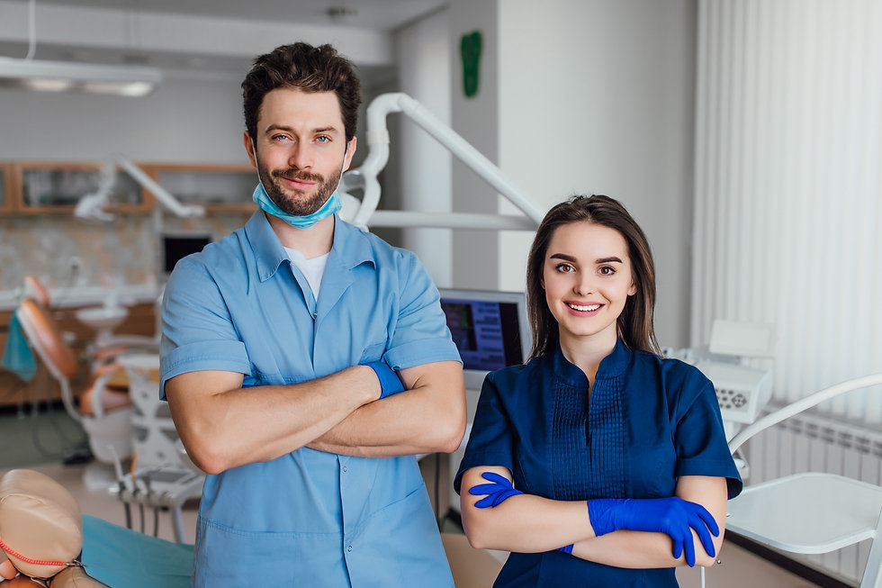 portrait-smiling-dentist-standing-with-arms-crossed-with-her-colleague.jpg