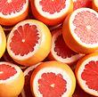 Many sliced fresh grapefruits as backgro