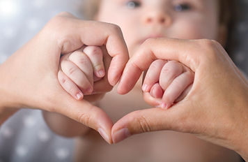 Newborn baby holding mother hands in hea