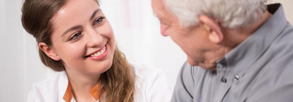 medivita Mitarbeiterin spricht mit Patient