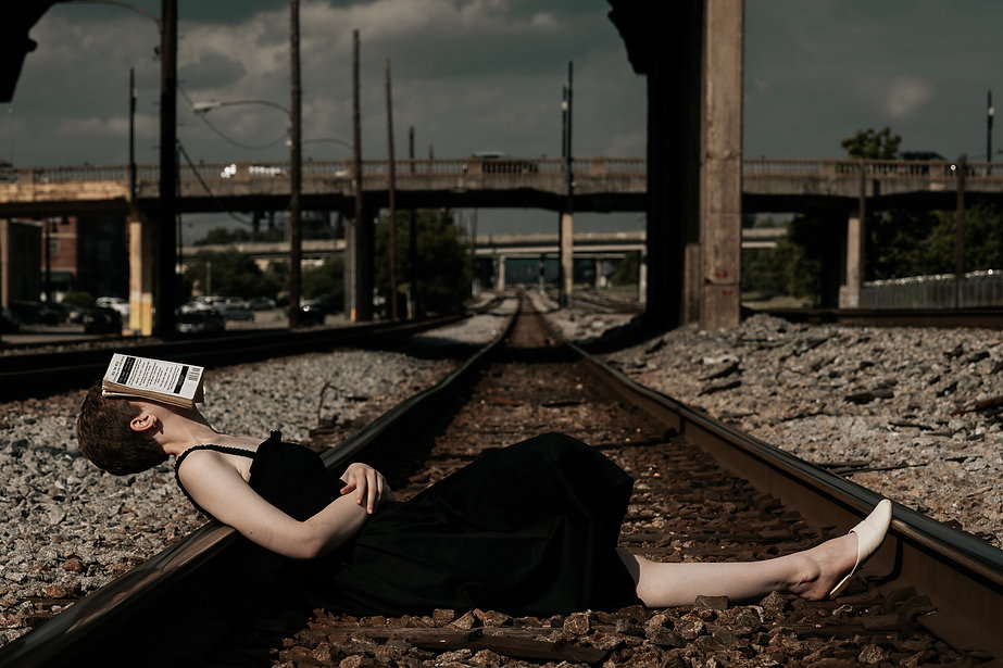 This is a photo of a beautiful girl lying a set of traintrack with a book hiding her face. I like to think this photo is tells a story of how we are all blind to the dangers around us and how we unknowingly choose what feeds our complacency.