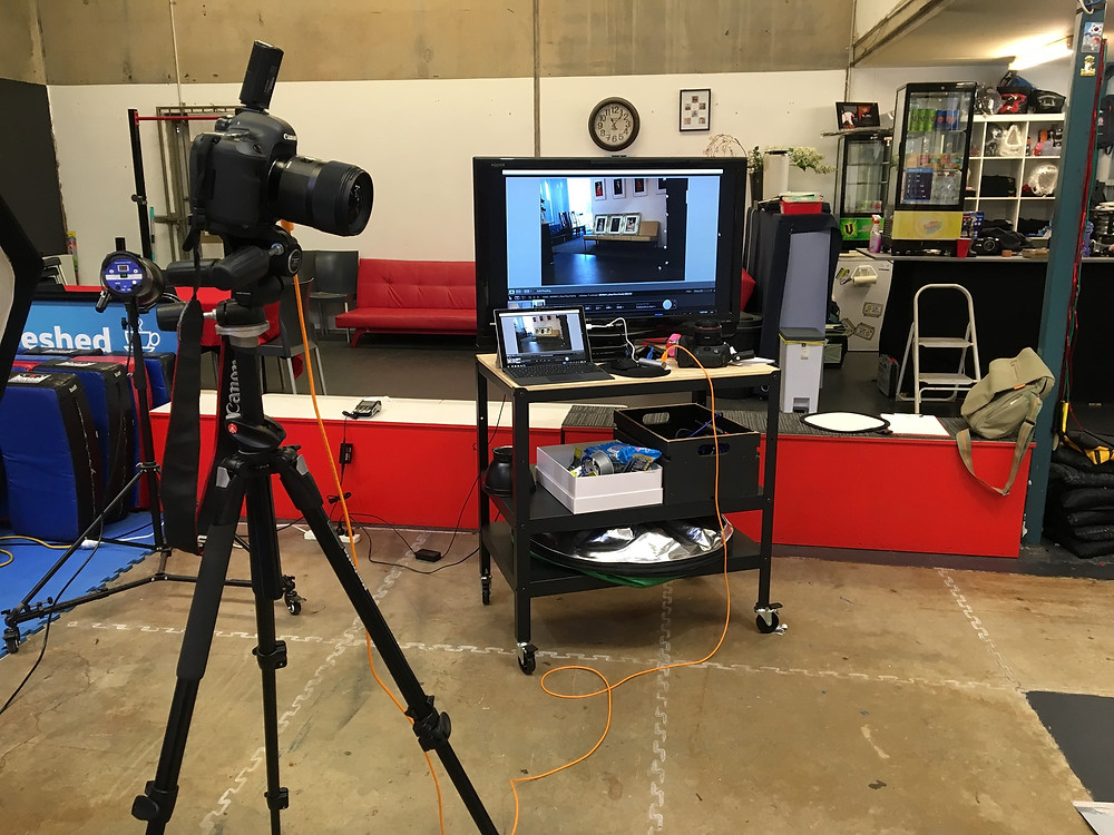 A camera on a tripod is tethered by an orange cable to a laptop which is connected to a tv screen displaying the last photo taken by the camera